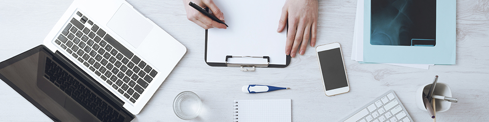 Professional doctor writing medical records on a clipboard with computer and medical equipment all around, desktop top view
